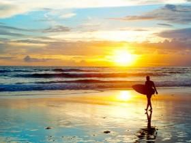Bali-Surfer-on-the-ocean-beach-at-sunset-shutterstock_1392766821