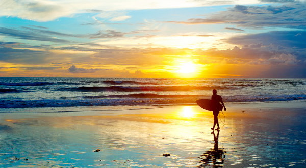 Bali-Surfer-on-the-ocean-beach-at-sunset-shutterstock_1392766821